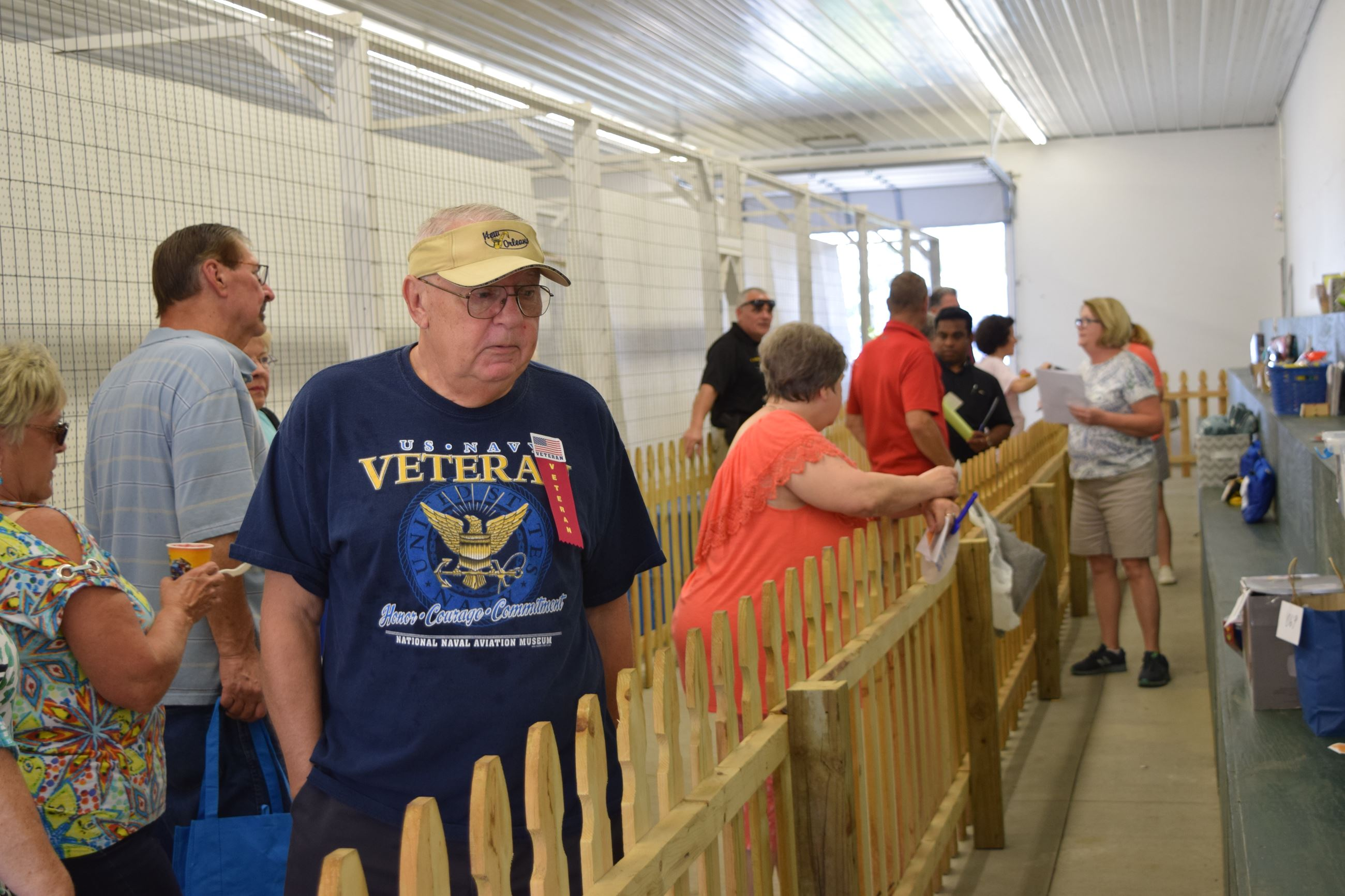 People lined up by an indoor fence